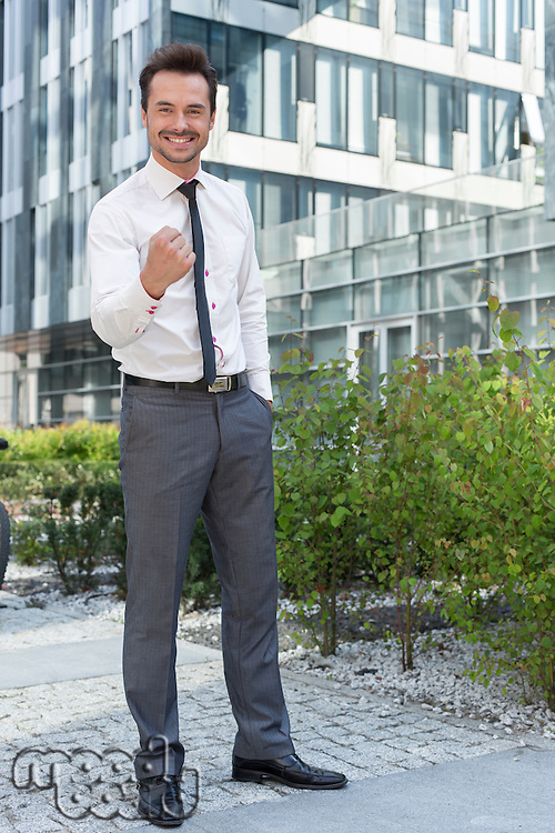 Full length portrait of successful businessman outside office building