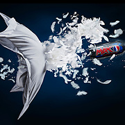 Bottle of Pepsi Max exploding Through a pillow and feathers flying everywhere Ray Massey is an established, award winning, UK professional  photographer, shooting creative advertising and editorial images from his stunning studio in a converted church in Camden Town, London NW1. Ray Massey specialises in drinks and liquids, still life and hands, product, gymnastics, special effects (sfx) and location photography. He is particularly known for dynamic high speed action shots of pours, bubbles, splashes and explosions in beers, champagnes, sodas, cocktails and beverages of all descriptions, as well as perfumes, paint, ink, water – even ice! Ray Massey works throughout the world with advertising agencies, designers, design groups, PR companies and directly with clients. He regularly manages the entire creative process, including post-production composition, manipulation and retouching, working with his team of retouchers to produce final images ready for publication.