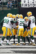 The Green Bay Packers celebrate, drawing a flag and a 15 yard penalty for unsportsmanlike conduct, after Green Bay Packers strong safety Micah Hyde (33) intercepts a first quarter pass and runs it down to the Oakland Raiders 2 yard line during the 2015 week 15 regular season NFL football game against the Oakland Raiders on Sunday, Dec. 20, 2015 in Oakland, Calif. The Packers won the game 30-20. (©Paul Anthony Spinelli)