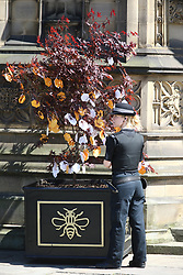 © Licensed to London News Pictures. 22/05/2018. Manchester, UK. A police woman attaches a message to a tree at the memorial service at Manchester cathedral. Today marks the first anniversary of the Manchester Arena bombing. 22 people died when Salman Abedi detonated a bomb at an Ariana Grande concert. Photo credit: Andrew McCaren/LNP