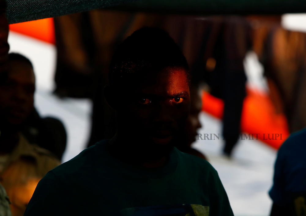 A migrant takes part in an impromptu prayer meeting at the stern of the Medecins san Frontiere (MSF) rescue ship Bourbon Argos somewhere between Libya and Sicily at sunset August 8, 2015.  Some 241 mostly West African migrants on the ship are expected to arrive on the Italian island of Sicily on Sunday morning, according to MSF.<br /> REUTERS/Darrin Zammit Lupi <br /> MALTA OUT. NO COMMERCIAL OR EDITORIAL SALES IN MALTA