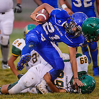 Laguna Acoma Hawk Isaiah Martinez (21) is pulled down by Thoreau Hawk Wyatt Largo (89) Friday at Grants High School.