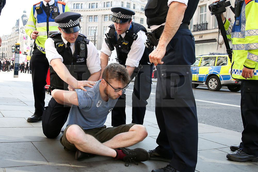 © Licensed to London News Pictures. 19/04/2019. London, UK. An environmental activist is detained by the police in Oxford Circus on the fifth day of the climate change protest by the Extinction Rebellion movement group. A large number of police presence around the pink boat as they un-bonding the activist who glued themselves and the police prepare to remove  from the site. According to the Met Police, over 700 activists have been detained over the past five days.  Photo credit: Dinendra Haria/LNP