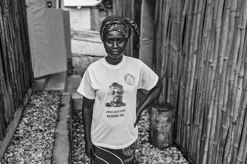 Community Health Worker wears a t shirt that mourns a dead colleague.  John Logan Town, Liberia.