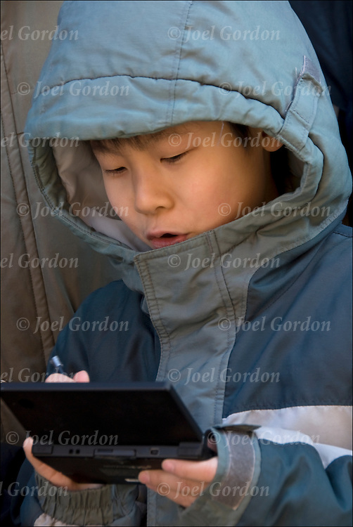 Chinese American boy in crowd watching parade and playing with hand held game console electronic device, looking at the built-in screen