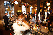 New York, NY - April 11, 2015: A bartender shakes cocktails at a reception during the Food Book Fair in the Wythe Hotel. The Food Book Fair, dubbed the 'Coachella of writing about eating' by organizer Kimberly Chou, brings together authors, chefs, publishers and food aficionados to discuss the state of food publishing.<br /> <br /> &copy; CREDIT: Clay Williams for Food Book Fair.<br /> <br /> Clay Williams / claywilliamsphoto.com