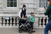 Two young boys wearing plastic police helmets are made happy by a real-life police officer outside the Cabinet Office on Whitehall in Westminster, on 28th August 2019, in London, England.