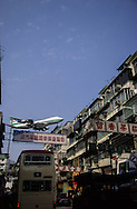 Hong Kong. Plane Flying Over Buildings A plane flies low over the Ma Tau Wai area of Kowloon, ., planes landing on Kai tak airport in the city CENTER over the buildings .      / Des avions au ras des buildings. Avion atterrissant en plein milieu de la ville sur L'ANCIEN aéroport  DE Kai Tak (QUARTIER MONGKOK) / Dans la ville de Hong-Kong surpeuplée, l'avion est le principal moyen d'accès à la ville. La seule piste d'atterrissage est en pleine ville       / R82/25    L1074  /  R00082  /  p0006066