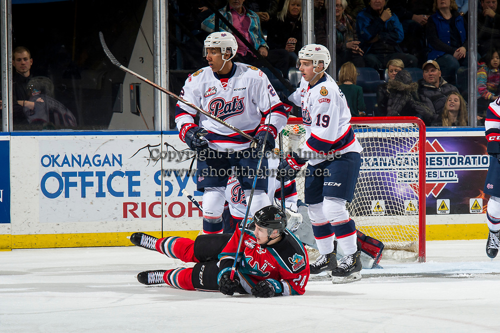 KELOWNA, CANADA - NOVEMBER 21: Kyle Topping #24 of the Kelowna Rockets falls to the ice after a check by Aaron Hyman #2 and Jake Leschyshyn #19 of the Regina Pats during first period on November 21, 2018 at Prospera Place in Kelowna, British Columbia, Canada.  (Photo by Marissa Baecker/Shoot the Breeze)