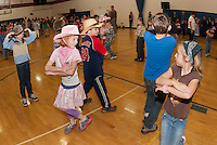 "Caylin Seely (pink) and Bailey Kucckowski ""Do Si Do"" on the Inter Lakes Elementary School gymnasium/dance floor for the annual Square Dance Thursday afternoon.  (Karen Bobotas/for the Laconia Daily Sun)"