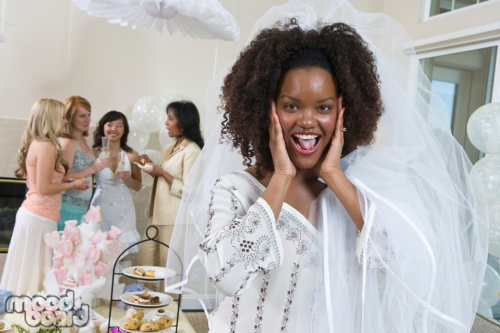 Excited bride wearing veil at bridal shower