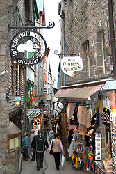 Grande Rue, narrow as a cow path, runs through the commercial heart of Mont-Saint-Michel, on the border between Normandy and Brittany in western France.