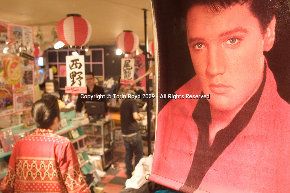 "Seen here is rockabilly and Elvis songster Shinji Tamura, of Tokyo, helping to pack up the now closed Elvis memorabilia shop called Love Me Tender  the day after it it closed for good. For the past 24 years this shop has been a Tokyo institution dedicated to Elvis Presley. Located in Tokyo's trendy youth hangout of Harajuku, this shop has been a mecca for Japanese Elvis fans as well as a popular attraction for foreign tourists. But on Sunday January 18, 2009 it all came to an end when Love Me Tender closed it doors for good. According to staff who worked here, Love Me Tender closed for a number of reasons citing the bad economy as well as the land being an attractive prize for real estate speculators. In addition to this shop, also housed here was a Rolling Stones shop called Gimme Shelter and a Beatles shop called Get Back. Collectively the building was called The Rock 'N' Roll Museum. Just in front was a larger than life sized bronze statue of Elvis which had been there since 1992. Sadly ""Elvis Left the Building"" the same day when only a handful of people were on hand to witness the King being hauled away. For now, the Elvis statue will be kept in storage while the shop's owners can find a permanent home for him. Their ideal location would be in front of Harajuku Station which is sort of a landmark for rock and roll in Japan. After WW II the American military built a large housing project there for military families and during the 1950s and 1960s American teenage subculture flourished here."