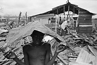 1979, San Cristobal, Dominican Republic --- A young boy stands amid rubble left from a ruined house sheltering himself under a piece of scrap metal. --- Image by © Owen Franken/CORBIS