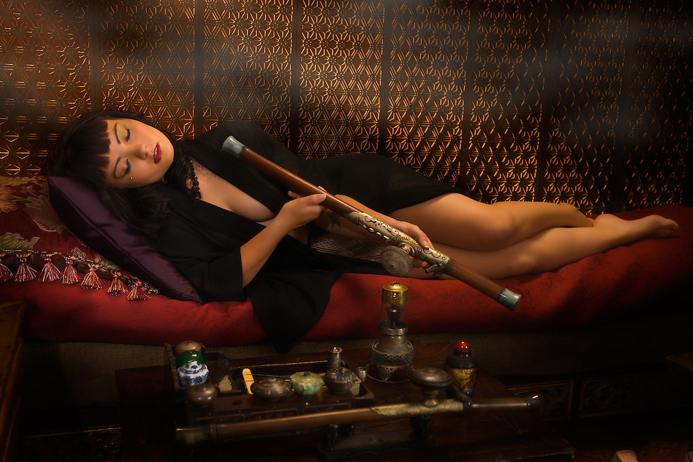 "Am I not desirable? Seductive, beautiful woman portrayed by alternative model Sabrina Sin, smoking opium in an ornate pipe, a forbidden pleaure among the liberated French females of the 1930's. She is being carried away by the effects of the drug surrendering herself to the drug. This collection was inspired by the writings of Brassai in his book ""The Secret Paris of the 1930's""."