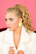 Closeup of fashion model Brenna Smith wearing designer pompom earrings.