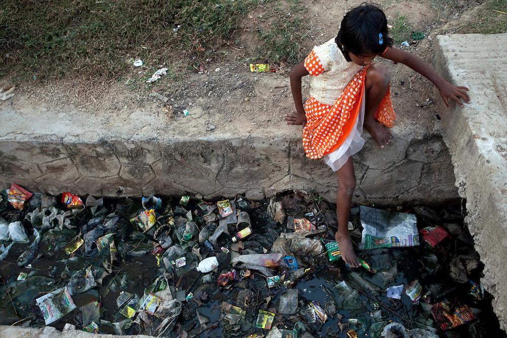 A dalit girl plays next to a drain, inside the Tamil Nadu Slum Clearance Board quarters 20 kms away  in Kannagi Nagar in Chennai, India, on Friday, January 14, 2011. Photographer: Prashanth Vishwanathan/HELSINGIN SANOMAT