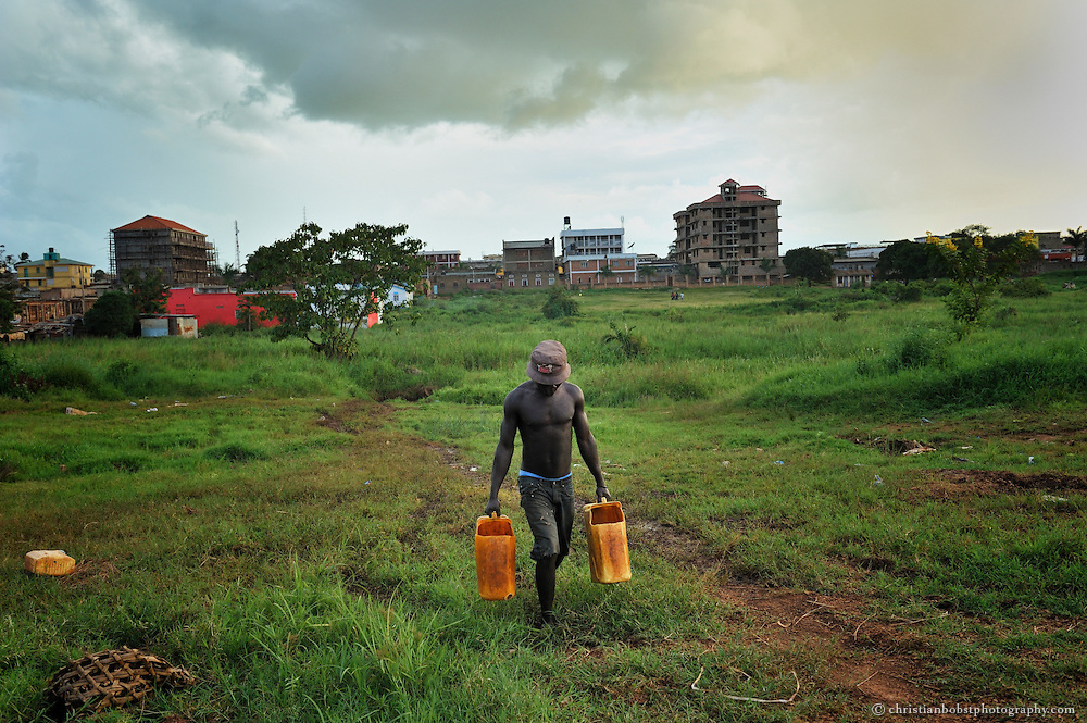Outside the center of Gulu city, a man carries water to his home. Gulu was at the heart  of the conflict between the rebels and the ugandan army.