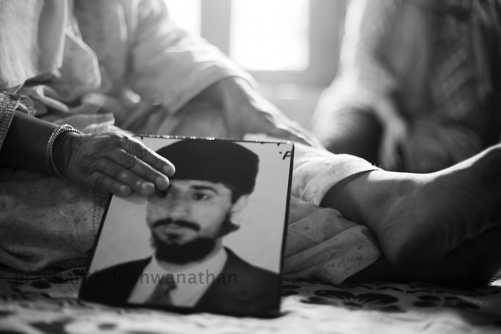 A mother holds onto a photo of her son taken away for questioning 14 years ago, September 2011, Kashmir, India. Photographer: Prashanth Vishwanathan