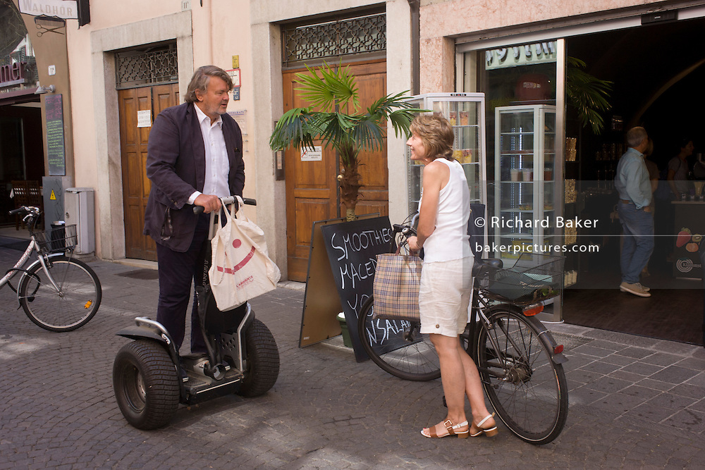 A Segway rider chats to a shopper with bicycle in the northern Italian south Tyrolean city of Bozen-Bolzano.