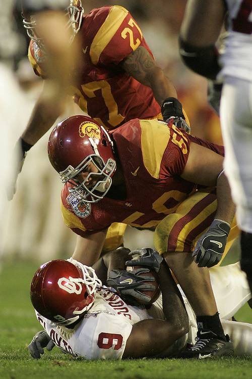 University of Southern California linebacker Lofa Tatupu tackles Oklahoma University wide receiver Mark Clayton <br /> during USC's 55-19 victory over Oklahoma on January 4, 2005 in the FedEx Orange Bowl at Pro Player Stadium in Miami, Florida.