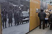 "Visitors learning about the Berlin Wall read outdoor exhibition panels near the former Checkpoint Charlie, the former border between Communist East and West Berlin during the Cold War. The Berlin Wall was a barrier constructed by the German Democratic Republic (GDR, East Germany) starting on 13 August 1961, that completely cut off (by land) West Berlin from surrounding East Germany and from East Berlin. The Eastern Bloc claimed that the wall was erected to protect its population from fascist elements conspiring to prevent the ""will of the people"" in building a socialist state in East Germany. In practice, the Wall served to prevent the massive emigration and defection that marked Germany and the communist Eastern Bloc during the post-World War II period."