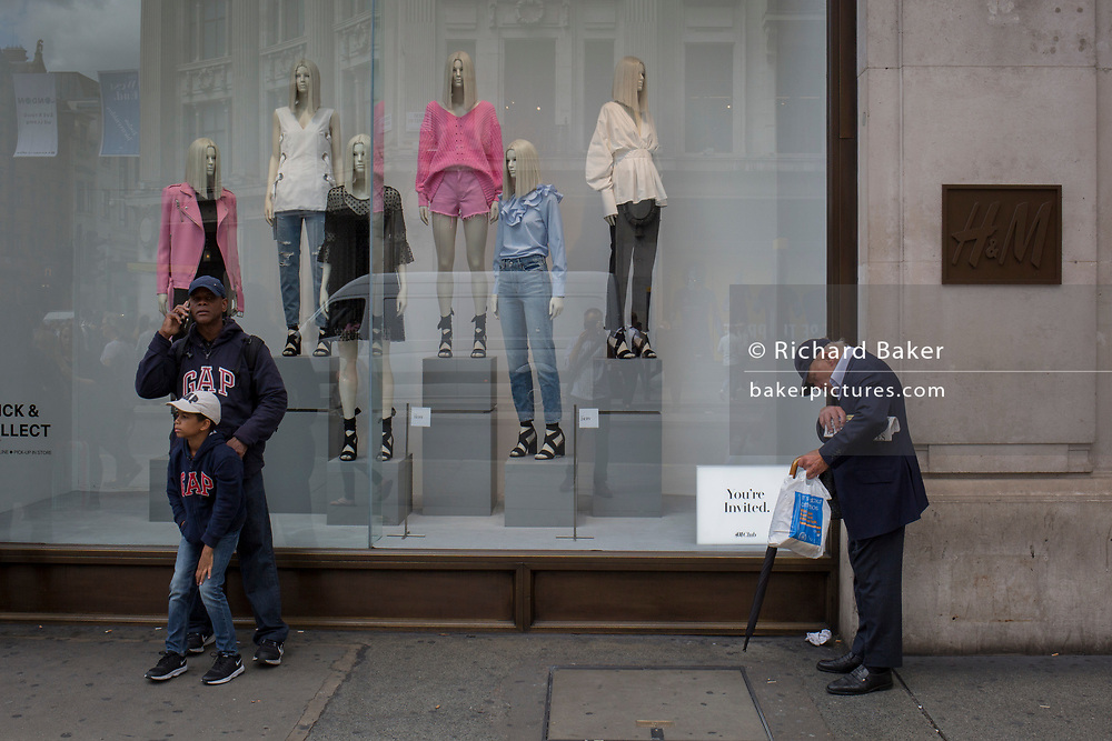 A father and son wearing identical GAP tops stand outside H&M,, on 31st July 2017, in Oxford Street, London, England.