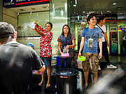 13 APRIL 2018 - BANGKOK, THAILAND:  Thais throw water on tourists during a water fight on Silom Road on the first day of Songkran in Bangkok. Songkran is the traditional Thai New Year celebration best known for water fights.     PHOTO BY JACK KURTZ