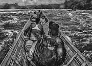 Fleuve Oyapock, 2015.<br /> <br /> Pirogue guyanaise &laquo; l&eacute;gale &raquo;, franchissement d&rsquo;un saut. Ici, pas de route, le transport fluvial repr&eacute;sente la seule liaison r&eacute;guli&egrave;re possible entre les communes enclav&eacute;es le long de l&rsquo;Oyapock. Ce fleuve est pourtant juridiquement consid&eacute;r&eacute; comme non navigable. <br /> <br /> La navigation sur l&rsquo;Oyapock n&eacute;cessite le franchissement de nombreux &laquo; sauts &raquo;, des barrages naturels causes d&rsquo;accidents &agrave; r&eacute;p&eacute;tition. Les piroguiers doivent d&eacute;terminer leur trajectoire sur un fleuve o&ugrave; aucun chenal n&rsquo;est balis&eacute; et o&ugrave; de nombreuses roches affleurent et rendent la navigation difficile ou impossible. En saison s&egrave;che, les transports de fret doivent r&eacute;guli&egrave;rement d&eacute;poser leur cargaison sur la berge, porter la pirogue par voie terrestre jusqu&rsquo;&agrave; un point situ&eacute; apr&egrave;s le saut o&ugrave; la cargaison transport&eacute;e &agrave; pied rejoindra la pirogue.<br /> En saison des pluies, il faut compter cinq heures pour rejoindre Camopi depuis Saint-Georges de l&rsquo;Oyapock &agrave; deux cents kilom&egrave;tres en aval si le voyage s&rsquo;effectue sans encombre, en saison s&egrave;che, le m&ecirc;me trajet peut durer deux ou trois jours.<br /> <br /> Dans ce contexte, dans les pirogues une certaine solidarit&eacute; pr&eacute;vaut sur des consid&eacute;rations d&rsquo;appartenance nationale, fran&ccedil;ais guyanais, br&eacute;siliens clandestins ou pas et am&eacute;rindiens partagent les m&ecirc;mes contraintes.