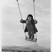 One of the young Heart Mountain school children is enjoying a swing on the center's play ground. -- Photographer: Iwasaki, Hikaru -- Heart Mountain, Wyoming. 11/24/43<br />