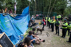Denham, UK. 24 July, 2020. Police officers from the Metropolitan Police and City of London Police occupy one bank of the river Colne to prevent environmental activists from HS2 Rebellion from attempting to hinder the destruction of an ancient mature alder tree in connection with works for the HS2 high-speed rail link in Denham Country Park. A large policing operation involving the Metropolitan Police, Thames Valley Police, City of London Police and Hampshire Police as well as the National Eviction Team was put in place to enable HS2 to remove the tree.