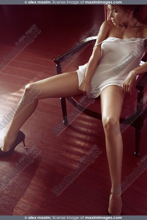 Artistic sensual photo of a beautiful young woman sitting in a bold seductive pose in a chair with her long sexy legs in high heel shoes spread wide apart