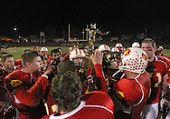 The Marion Indians gather around their trophy after their second round playoff football game at Thomas Park Field in Marion on Monday, October 29, 2012.