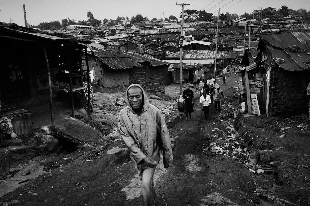 NAIROBI, KENYA - AUGUST 16, 2011: Kamau &quot;Kelly&quot; Ng'ang'a walks home through the winding dirt paths of Kibera slum.<br /> <br /> Within Kenya's progressive youth culture is the Kibera Olympic Boxing Club, a group of low-income adolescents from the slum whose leader uses boxing as a way to engage with idle youth. The group's ethnic diversity is remarkable given Kenya's 2008 post-election violence in which people from several tribes were forced violently out of slums. Together, these boxers represent a nascent trend of cross-tribe brotherhood in a healing nation.