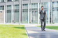 Businessman using cell phone while walking on path outside office