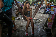 """Jocelyn Banting, a teenage widow, is 14 years old.  She lives and works in a bar next to the Market 3 slum in the Navotas Fish Port complex as a bar girl and sex worker.  Her partner, and father of her child, Alan Uba AKA, Boy Muslim, was gunned down in President Duterte's """"War on Drugs""""  Jocelyn's mother, Lenie Banting, 51, takes care of baby in her small hut on the former Smoky Mountain dump which has become a perverse island of green in a sea of slums.  Tondo, Manila, Philippines."""