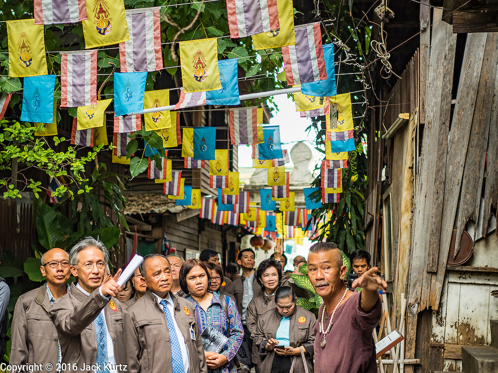 03 AUGUST 2016 - BANGKOK, THAILAND: TAWATCHAI VORAMAHAKUN, right gesturing, a community historian and leader in the Pom Mahakan slum, talks to WALLOP TANGKANA-NURAK, left, chairman of the National Legislative Assembly's (NLA) housing extraordinary committee, and other members of the NLA during a tour of the slum. Residents of the slum have been told they must leave the fort and that their community will be torn down. The community is known for fireworks, fighting cocks and bird cages. Mahakan Fort was built in 1783 during the reign of Siamese King Rama I. It was one of 14 fortresses designed to protect Bangkok from foreign invaders. Only of two are remaining, the others have been torn down. A community developed in the fort when people started building houses and moving into it during the reign of King Rama V (1868-1910). The land was expropriated by Bangkok city government in 1992, but the people living in the fort refused to move. In 2004 courts ruled against the residents and said the city could take the land. Eviction notices have been posted in the community and people given until April 30 to leave, but most residents have refused to move. Residents think Bangkok city officials will start evictions around August 15, but there has not been any official word from the city.      PHOTO BY JACK KURTZ
