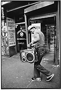 Boy carrying a boom box, 42nd Street, New York City, USA, 1980