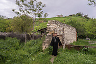 A priest from the Church of Mother Mary walks near his church on Sunday, May 8, 2016 in Talish, Nagorno-Karabakh. Due to intense nearby fighting in early April, the entire village has been evacuated of civilians.