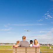 A local family watches planes take off from a bench at the Charlotte-Douglas airport overlook.
