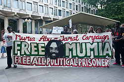 """Zimmerman's trial began on June 10, 2013, in Sanford. On July 13, 2013, he was found not guilty of second-degree murder and of manslaughter charges of Trayvon Martin.<br /> Demonstrators hold a banner reading """"Free Mumia - Free all political prisoners"""" outside the American Embassy to protest the recent Trayvon Martin's Verdict,<br /> London, United Kingdom<br /> Tuesday, 16 July 2013<br /> Picture by Piero Cruciatti / i-Images"""