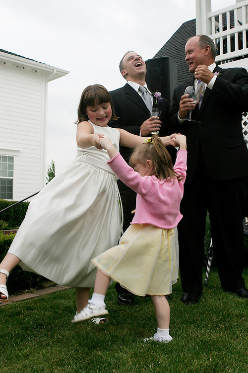 Flower girls dancing on the grass while groom laughs with a guest behind the elegant white Bed and Breakfast.