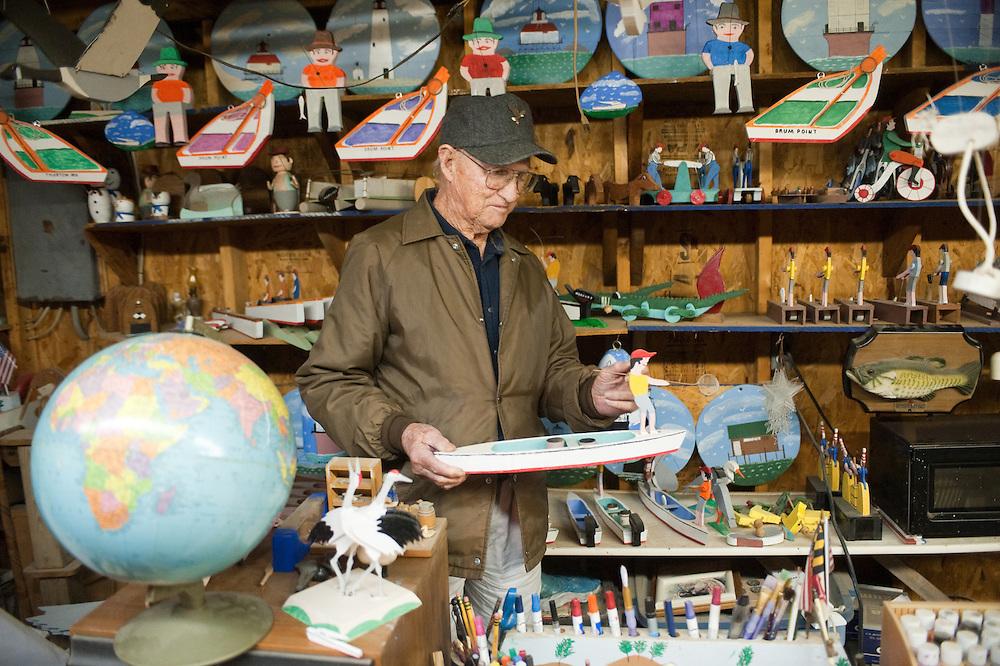 Man holding handmade boat in hobby shop