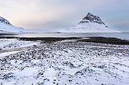 The mountain Kirkjufell and a lagoon of the northern Atlantic in the winter, village Grundarfjoerdur, Peninsula Snaefellsnes, Iceland