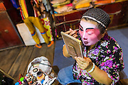 "19 AUGUST 2014 - BANGKOK, THAILAND:  A member of the Lehigh Leng Kaitoung Opera troupe applies her makeup before a performance at Chaomae Thapthim Shrine, a small Chinese shrine in a working class neighborhood of Bangkok. The performance was for Ghost Month. Chinese opera was once very popular in Thailand, where it is called ""Ngiew."" It is usually performed in the Teochew language. Millions of Chinese emigrated to Thailand (then Siam) in the 18th and 19th centuries and brought their culture with them. Recently the popularity of ngiew has faded as people turn to performances of opera on DVD or movies. There are still as many 30 Chinese opera troupes left in Bangkok and its environs. They are especially busy during Chinese New Year and Chinese holiday when they travel from Chinese temple to Chinese temple performing on stages they put up in streets near the temple, sometimes sleeping on hammocks they sling under their stage. Most of the Chinese operas from Bangkok travel to Malaysia for Ghost Month, leaving just a few to perform in Bangkok.            PHOTO BY JACK KURTZ"