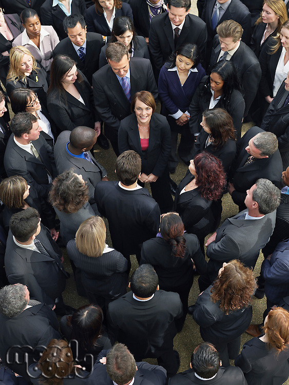 Large group of business people surrounding woman looking up elevated view