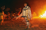 An Apache girl dressed in traditional buckskin clothes dances beside a bonfire at a Sunrise Dance, a first menstruation rite, on the San Carlos Apache Reservation, Arizona, USA. The figures in the background are mountain spirits (gaan) or crown dancers. The girl is not the young girl for whom the puberty rite is held, but one of four girls chosen to dance with her and the mountain spirits by the evening bonfire. The Sunrise Dance is held during the summer, within one year after the girl has had her first menstruation, and lasts for four days. The ceremony is an enactment of the Apache creation myth and during the rites the girl 'becomes' Changing Woman, a mythical female figure, and comes into possession of her healing powers. The rites are also supposed to prepare the girl for adulthood and to give her a long and healthy life without material wants.