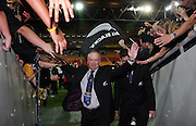 All Black coach Graham Henry celebrates with fans as he leaves the field.<br />