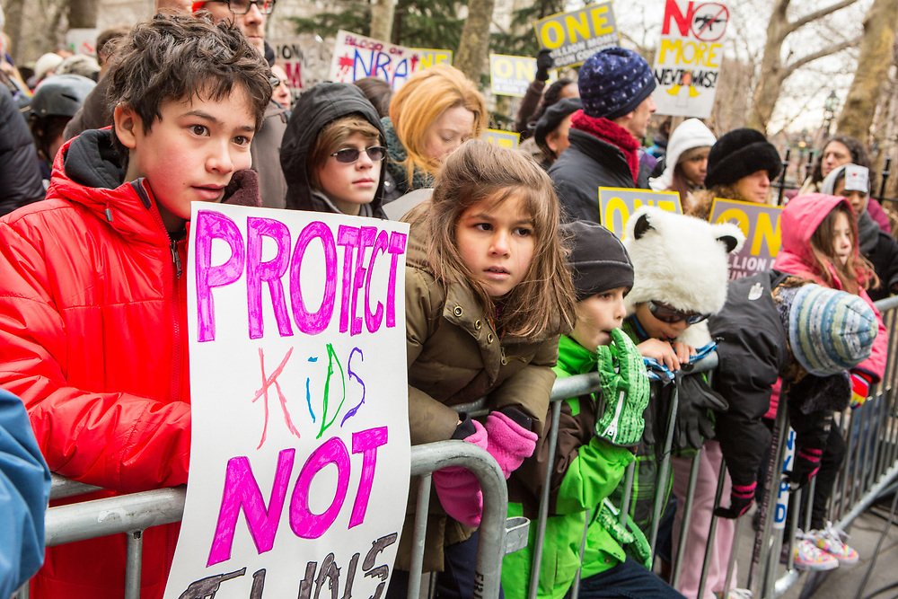 Near City Hall, children line the fence to hear the speakers.