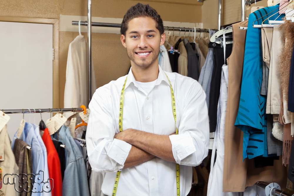 Portrait of handsome young tailor with arms crossed standing in front of clothes rail